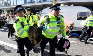 Police officers carry away an activist as Extinction Rebellion protesters block a road with caravan in central London