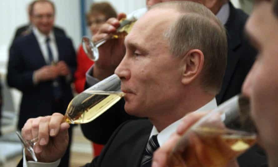 Vladimir Putin drinks champagne during an awards ceremony at the Kremlin