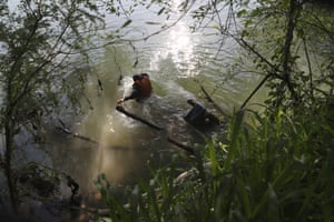 An immigrant wades across the Rio Grande