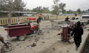 Local residents survey the scene in the aftermath of the suicide bombing in Khost province