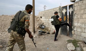 Turkey-backed Syrian fighters break open the front door of a house in Ras al-Ayn, a town now abandoned by Kurdish forces.