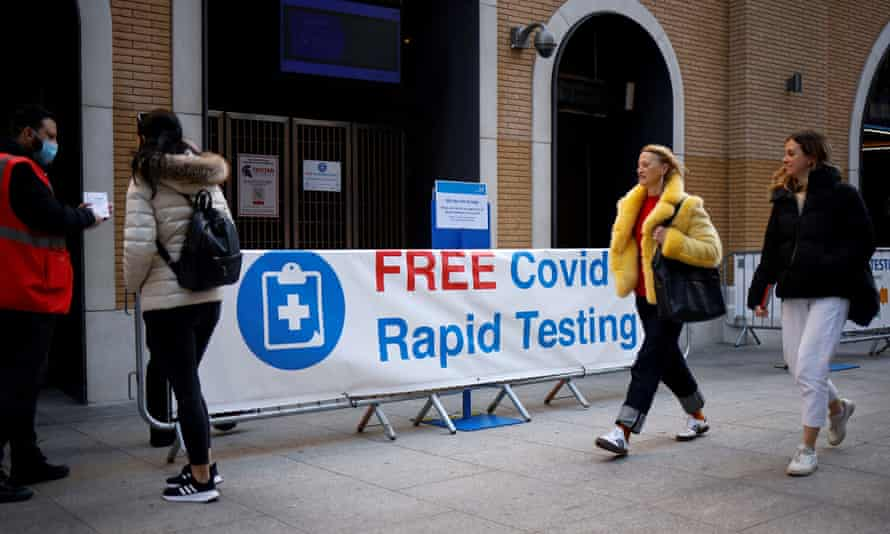 People walk past a sign directing people to a rapid lateral flow Covid-19 testing centre at London Bridge station