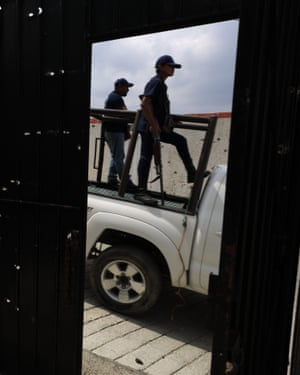 FUPCEG vigilantes drive past the bullet hole-riddled gate to a home where heavy fighting took place, in Filo de Caballos.