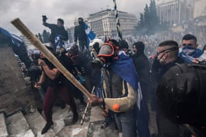 Protesters outside the Greek parliament wear gas masks in Athens