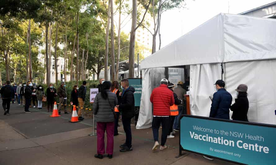 People wearing masks queue outside a NSW Health vaccination centre