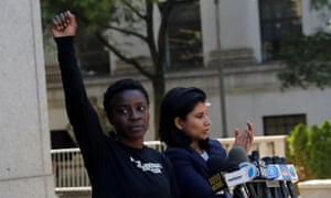 Patricia Okoumou raises her hand in the air after leaving federal court from her arraignment.