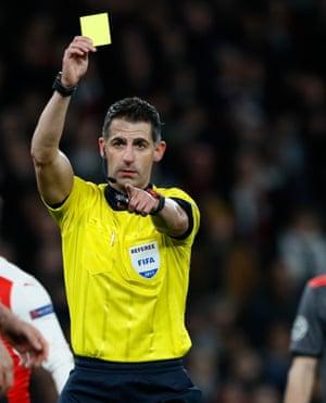 Referee Anastasios Sidiropoulos shows a yellow card