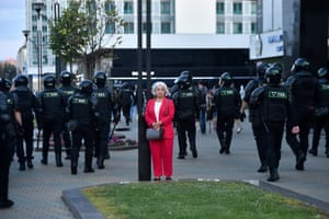 A woman stands among riot police during a rally of opposition supporters