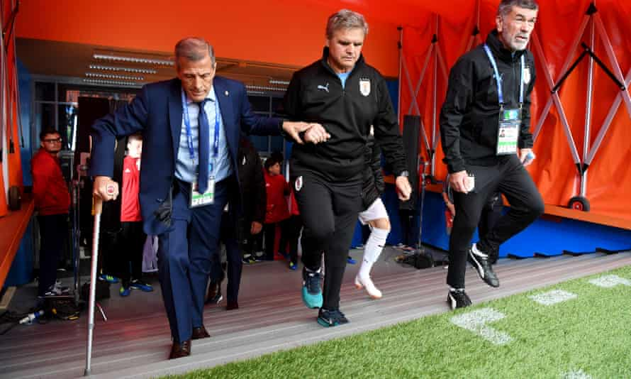 Óscar Tabárez, in his second spell as Uruguay manager, is helped to the pitchside for his team's opening World Cup game against Egypt.