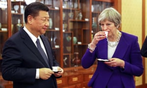 British Prime Minister Theresa May (R) drinks from a cup as she stands next to Xi Jinping, China's president, during a tea ceremony in Beijing, China