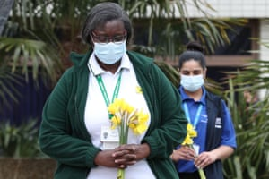 Members of staff hold floral tributes as they observe a minute's silence at St Thomas' Hospital, central London
