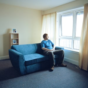 """Steven in his 'Homeless Flat' with photos of his nieces in the background. / In This Place (2016-17) When you move into a 'homeless flat' they feel all the same; same couch, same curtains, same furniture. Everybody knows when they come in that you're in 'the homeless'. When Steven moved into his flat, his youngest sister Chick gave him things to make it more like a home: """"...wee things like salt and pepper and mayonnaise and pictures of the weans (children)""""."""
