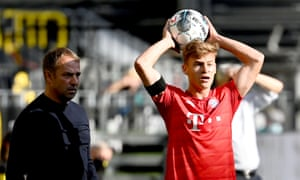 Joshua Kimmich takes a throw-in as his manager, Hansi Flick, looks on.