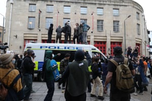 Protestors on top of a police van in front of Bridewell police station.