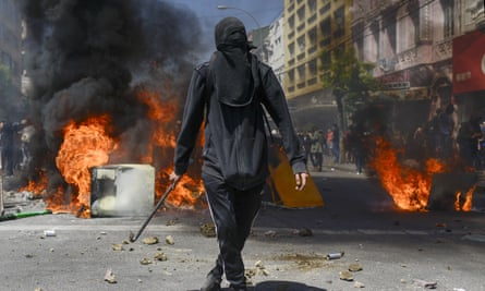 An anti-government protester stands in front of burning barricades in Valparaiso, Chile, on Thursday.