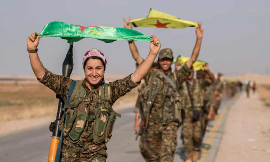 Kurdish fighters carry their parties' flags in Tel Abyad after capturing the town from Islamic State last year.