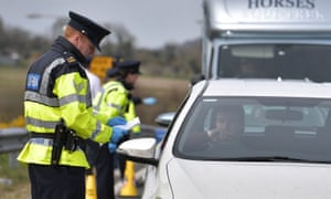 Police officers check for people engaging in non-essential travel outside the border town of Newry
