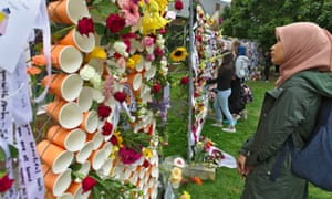 Students view tributes hung on wire fences to the victims of twin terror attacks targeting Al Noor and Linwood mosques in Christchurch.