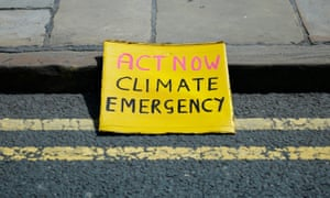 A placard rests on the kerb as members of Extinction Rebellion block the Neville Street Bridge in Leeds