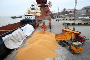 Workers loading imported soybeans onto trucks at a port in Nantong in China's eastern Jiangsu province.