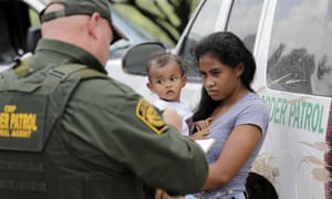A mother migrating from Honduras holds her 1-year-old child as she surrenders to US Border Patrol agents after illegally crossing the border, near McAllen, Texas.