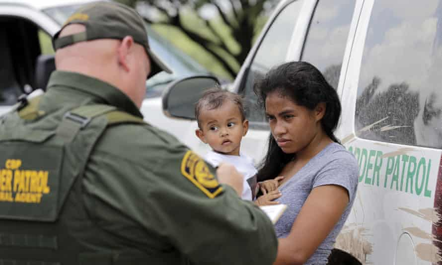 In this photo from 25 June 2018, a mother migrating from Honduras holds her one-year-old child as she surrenders to US border patrol agents after illegally crossing the border, near McAllen, Texas.