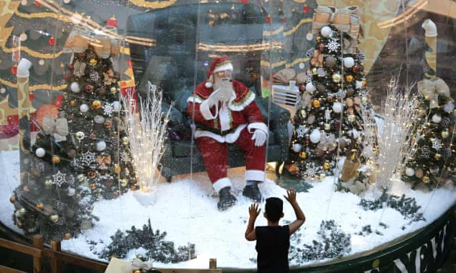 In an emergency, break the glass: a Santa Claus artist greets from behind a screen in Brasilia.