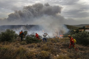 Firefighters and volunteers try to extinguish the flames in Penteli