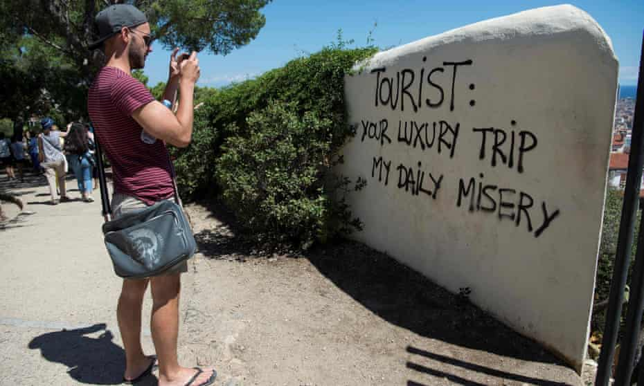 Graffiti at Park Güell in Barcelona reflects local feelings about the overwhelming number of tourists in the city.