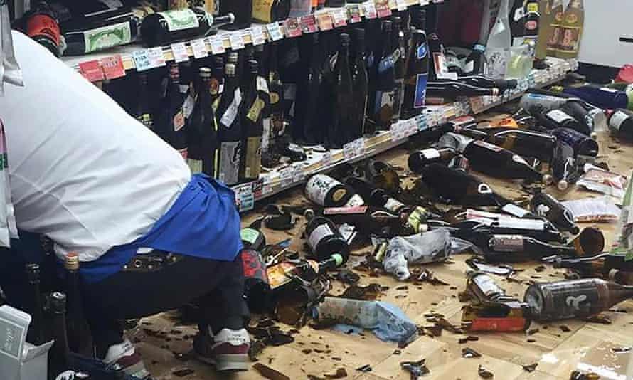 A shop clerk cleans broken wine bottles after the quake.