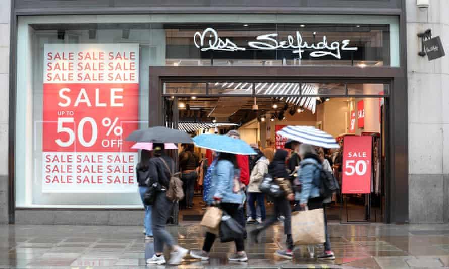 Pedestrians and shoppers walk past a Miss Selfridge store.