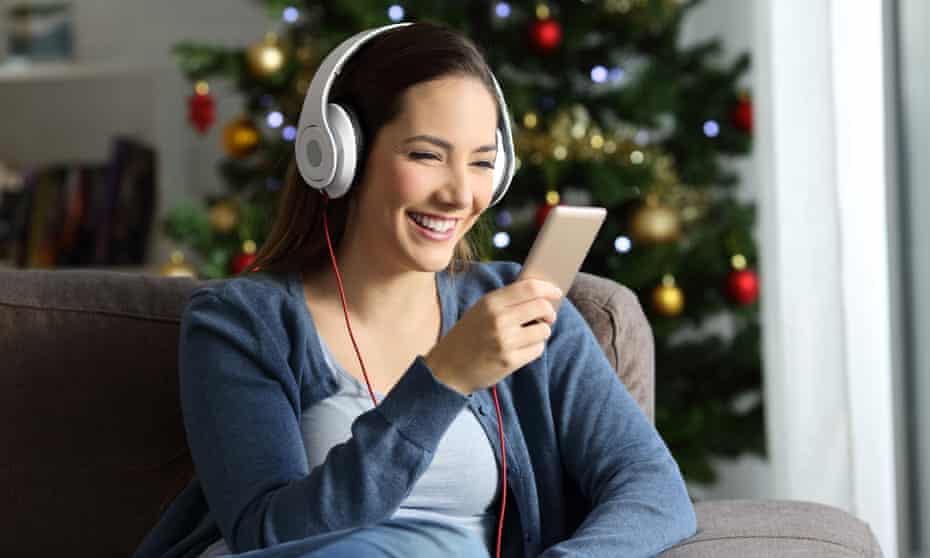 Happy woman wearing headphones listening to music at Christmas