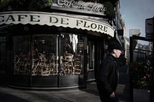 A man walks past the closed Café de Flore in Paris