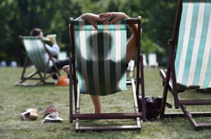 People relax in Green Park, west London