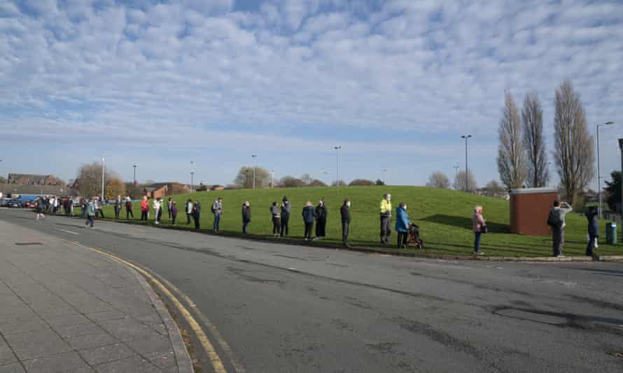 People queue at Liverpool Tennis Centre on the first day of a pilot scheme for mass testing.