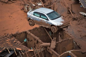 Car balanced on a house covered in mud in the aftermath of the Brazilian mining tragedy