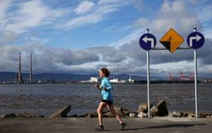A jogger on the Bull Wall in Dublin, Ireland