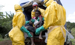 Health workers in Guinea assist a patient suspected of having Ebola