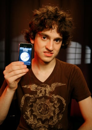 George Hotz, a notable hacker, is pictured in 2007 at age 17. He holds an iPhone after breaking the lock that ties Apple's iPhone to AT&T's wireless network, freeing it for use on the networks of other carriers.