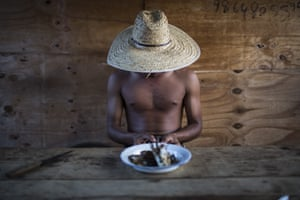 Diamond miner Rafael sits down to eat fish. Locals estimate there are hundreds of people across the region digging for diamonds in groups of 10 or less