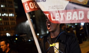 A protester marches follwing a mistrial verdict in the Freddie Gray trial.