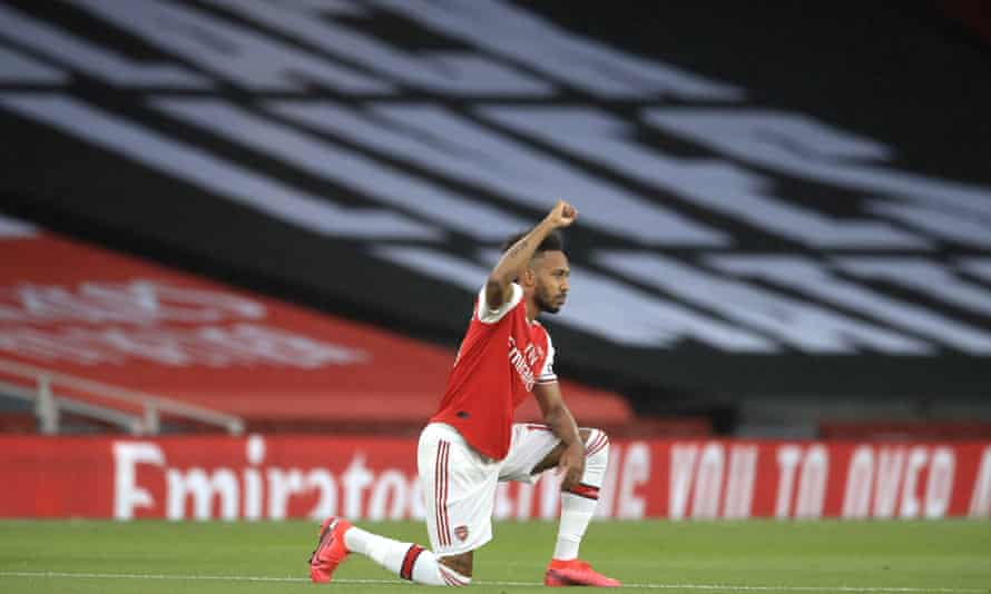 Arsenal's Pierre-Emerick Aubameyang kneels before a Premier League game with a Black Lives Matter banner in the background at the Emirates