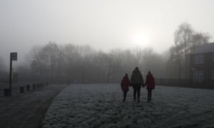 People walk through the Gateacre estate in Liverpool, with frost on the ground.