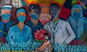 A man on a bicycle passes a mural depicting Covid-19 coronavirus front line workers in Kathmandu, Nepal.