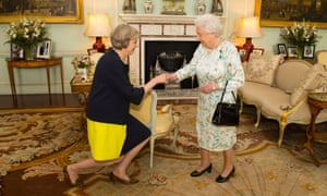 The Queen and a curtseying  Theresa May shake hands.