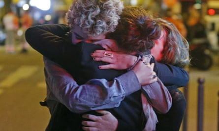 People hug on the street near the Bataclan concert hall after the attacks on 14 November 2015.