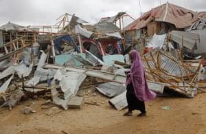 A woman walks near buildings destroyed by a car bomb in Mogadishu, Somalia