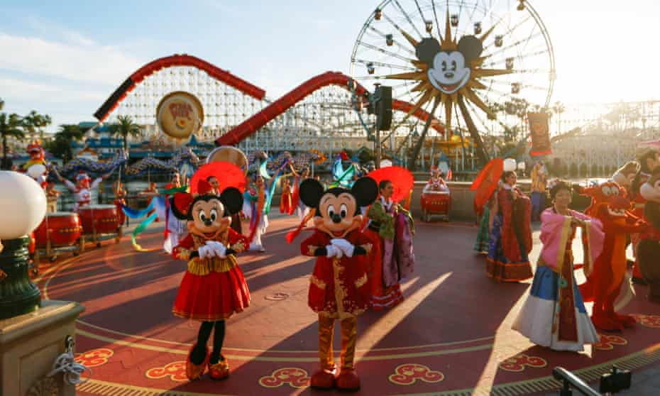 Mickey and Minnie Mouse greet visitors during lunar new year celebrations in the US. Theme parks in China have closed due to the virus outbreak.