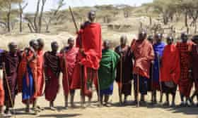 Maasai warriors wearing brightly coloured clothing perform traditional dance, Ngorongoro Crater Conservation Area Tanzania
