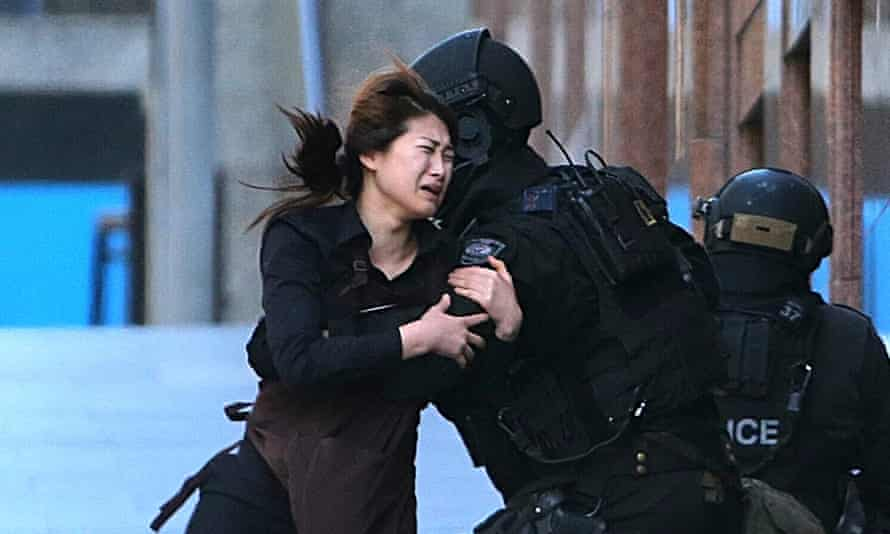 A hostage runs to armed police in Sydney.